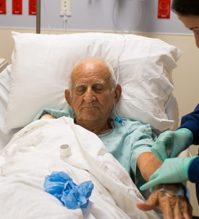hospitalized: Elderly 80 plus year old man recovering from surgery in a hospital bed