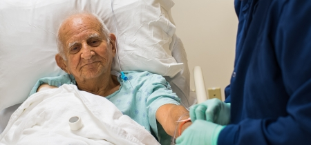 Elderly 80 plus year old man recovering from surgery in a hospital bed