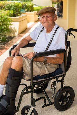 pierna rota: Hombre de 80 años más de edad avanzada con fractura de una pierna en una silla de ruedas al aire libre