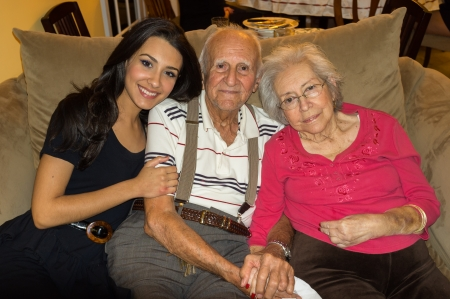 Elderly 80 plus year old grandparents with granddaughter in a home setting