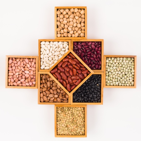 frijoles rojos: Colección de varios granos contenidos en cajas de madera sobre un fondo blanco Foto de archivo