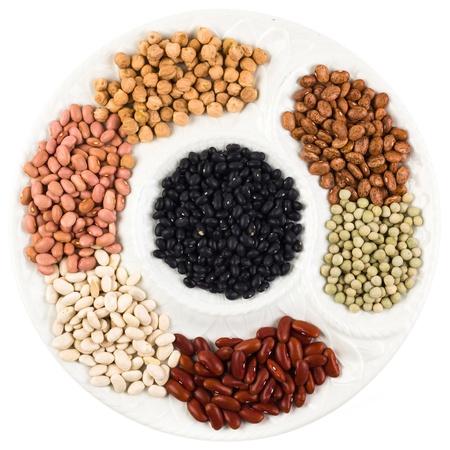 leguminosas: Colección de varios granos en un plato blanco redondo aislado en un fondo blanco Foto de archivo