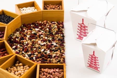 Mixed beans on a white background with individual beans in wood boxes next to chinese food take out boxes  photo