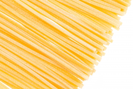 Close up view of freshly made linguine pasta on a white background