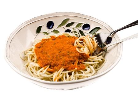 Close up van een kom van vers gekookte spaghetti pasta met een tomaten roomsaus op een witte achtergrond Stockfoto