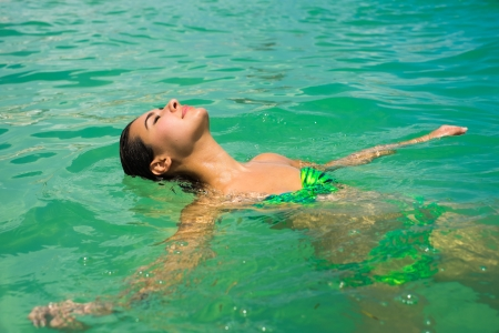 floating on water: Beautiful young multicultural woman relaxing in the water