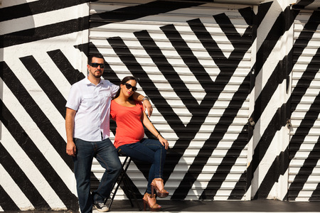 Young pregnant couple in a loving pose in a urban setting  photo