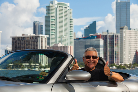 Handsome middle age man in a convertible automobile with a downtown skyline background. photo