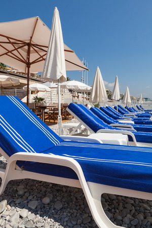 Colorful lounge chairs along the shoreline in Nice in the French Riviera. Stock Photo