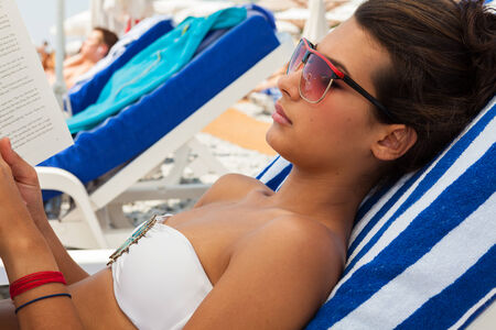 Beautiful young multicultural woman reading a book while lounging in the French Riviera