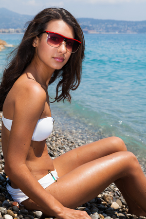 Beautiful young multicultural woman enjoying the beach in Nice in the French Riviera  photo