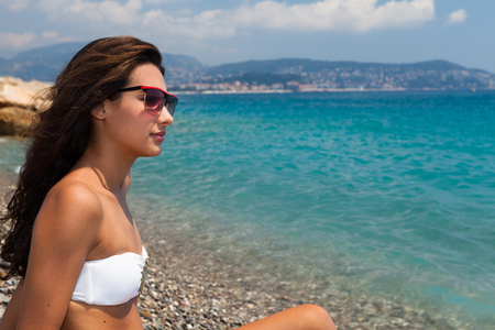 Beautiful young multicultural woman enjoying the beach in Nice in the French Riviera