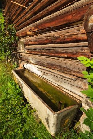 trough: Water trough in a rustic barn in a Swiss mountain valley  Stock Photo