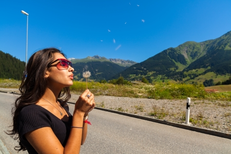 Beautiful young woman blowing a dandelion in the Swiss mountains. Stock Photo