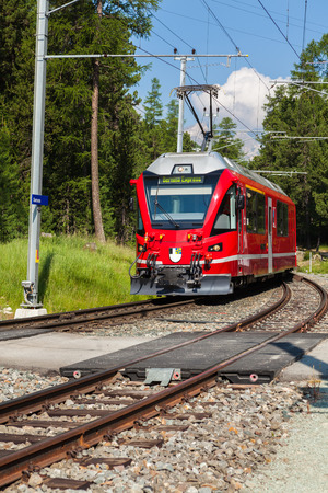 approaching: Swiss commuter train approaching a station in the Pontresina area of Switzerland