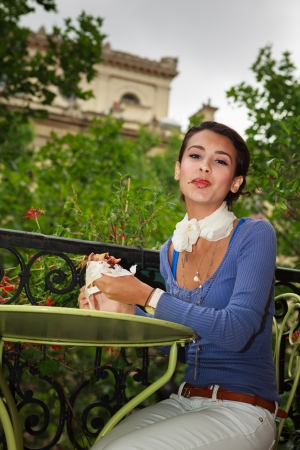 Beautiful young multicultural woman enjoying a french chocolate pastry on a balcony in Paris, France. Stock Photo