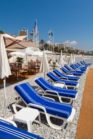 Colorful lounge chairs along the shoreline in Nice in the French Riviera. Editorial