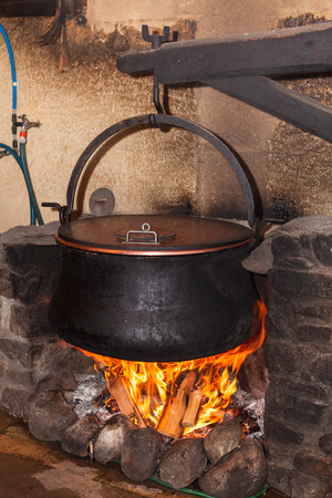 making a fire: Large boiling cauldron filled with milk and other ingredients for making fresh cheese on a swiss farm. Stock Photo