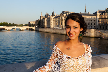 Beautiful young woman enjoying the sights of Paris by the River Seine.