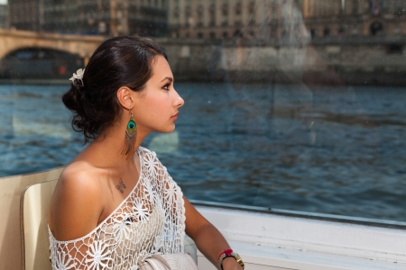 Beautiful young woman enjoying the sights of Paris in a water taxi on the River Seine.