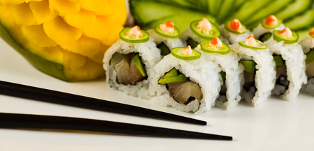 jalapeno pepper: Fancy spicy tuna sushi roll with avocado and jalapeno pepper on a white plate garnished with sliced cucumber and carved mango fruit. Stock Photo