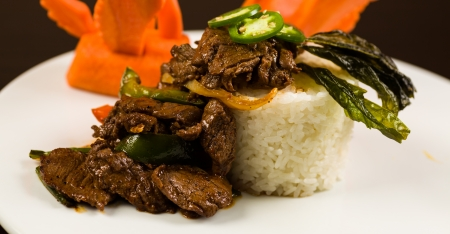 plating: Fancy sliced Asian pepper steak served with white rice and garnished with carved carrot swans on a white plate.