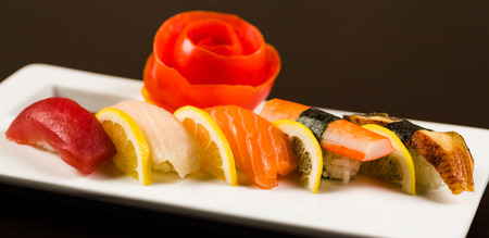 plating: Assorted fancy sashimi served on a white plate garnished with a sliced tomato. Stock Photo