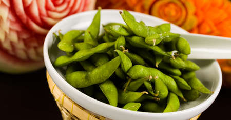 plating: Edamame served in a bowl with carved fruit in the background.