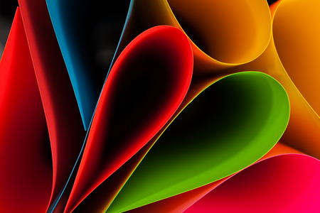 Colorful card stock in unique elliptical shapes with shadow effect and selective focus on a black background  photo