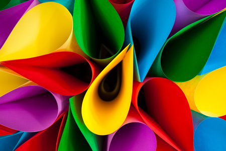 Colorful card stock in unique elliptical shapes with shadow effect and selective focus on a black background. photo
