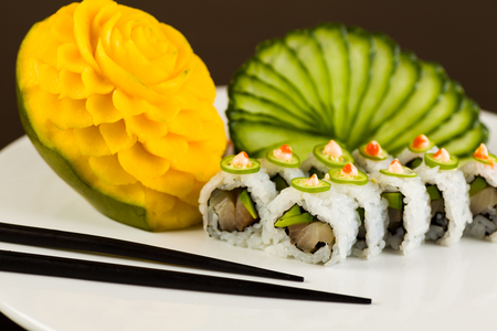 person appetizer: Fancy spicy tuna sushi roll with avocado and jalapeno pepper on a white plate garnished with sliced cucumber and carved mango fruit. Stock Photo