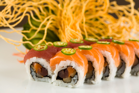 jalapeno pepper: Fancy tuna and salmon roll with jalapeno pepper on a white plate garnished with sliced cucumber and crispy noodles. Stock Photo