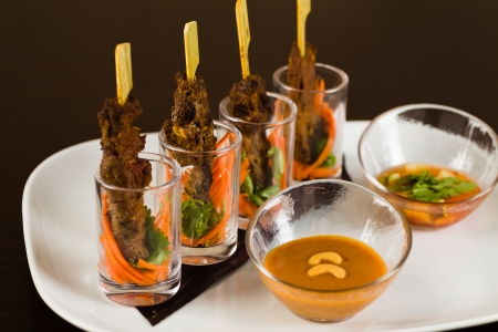person appetizer: Grilled Asian beef appetizer on a stick in small glasses with sliced vegetables on a white plate with sweet and spicy dipping sauces. Stock Photo