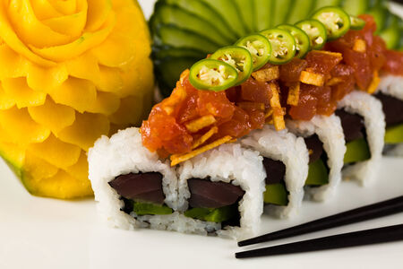 jalapeno pepper: Fancy spicy tuna roll roll with avocado and jalapeno pepper on a white plate garnished with sliced cucumber and carved mango