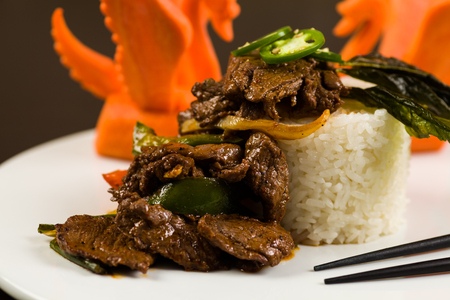 close up food: Fancy sliced Asian pepper steak served with white rice and garnished with carved carrot swans on a white plate