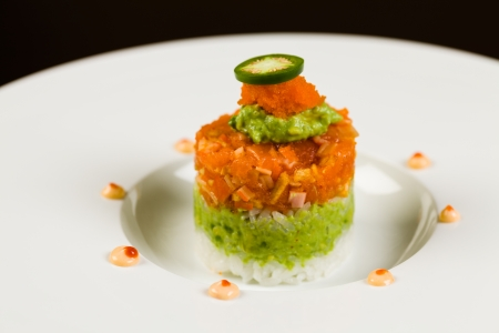 jalapeno pepper: Gourmet salmon and sushi tuna appetizer stacked on white rice on a white plate garnished with jalapeno pepper, guacamole and roe topping