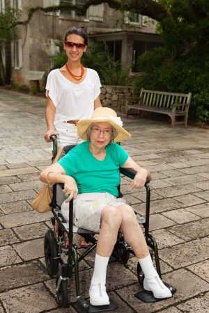 adult 80s: Grandmother with granddaughter in a garden setting. Stock Photo
