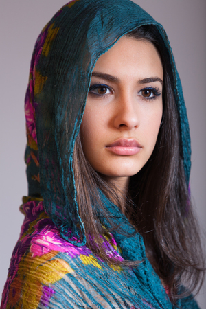 Beautiful multicultural young woman studio portrait wearing a purple veil. photo