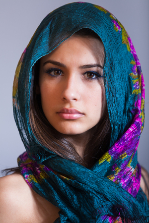 blue eyes girl: Beautiful multicultural young woman studio portrait wearing a purple veil