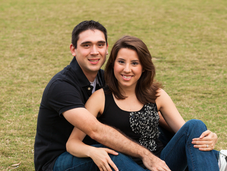 Young married couple  in a loving pose sitting on a lawn in a park. photo