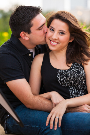 Young couple in a affectionate pose in a urban downtown park  setting. photo