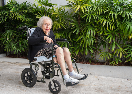 the elderly residence: Elderly eighty plus year old handicap woman in a outdoor setting.