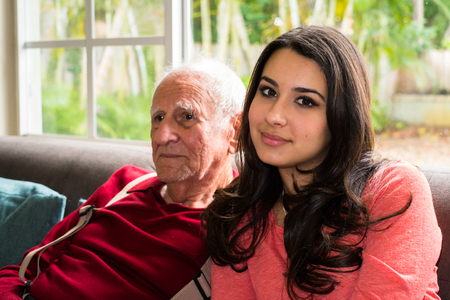 the elderly residence: Elderly eighty plus year old man with granddaughter in a home setting.