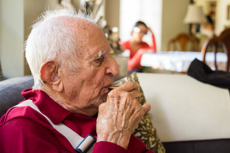 the elderly residence: Elderly eighty plus year old man drinking espresso coffee in a home setting.