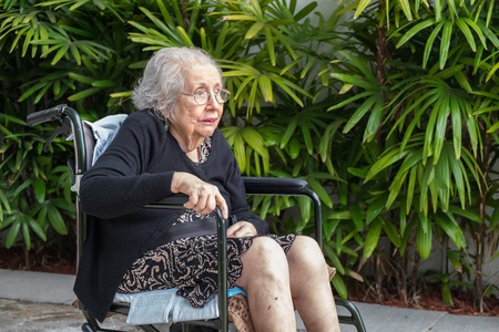 Elderly eighty plus year old handicap woman in a outdoor setting. photo