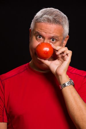 Handsome middle age man holding a tomato over his nose on a\ black background.
