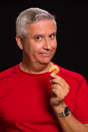 fortune cookie: Handsome middle age man holding a chinese fortune cookie on a black background. Stock Photo