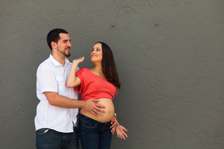 Young pregnant couple in a loving pose. photo