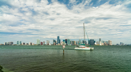 Beautiful Miami skyline along Biscayne Bay with sailboat crusing by. photo