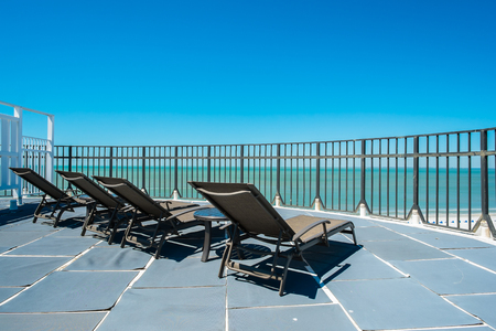 lounge: Lounge chairs on a rooftop penthouse apartment in the Florida west coast. Stock Photo